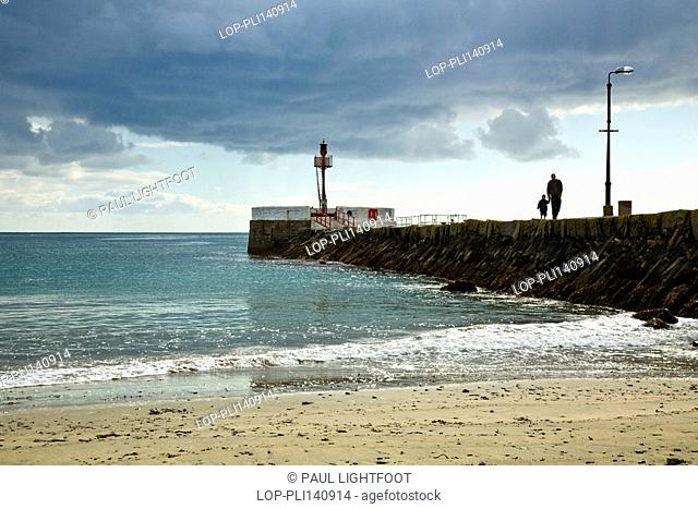 England, Cornwall, Looe, A father and young son walking under grey clouds along Looe's Banjo pier, with the beach in the foreground