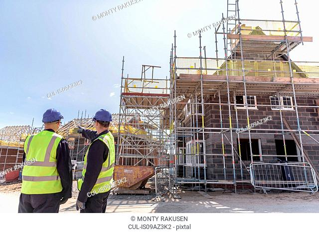 Builders discussing housing development on building site