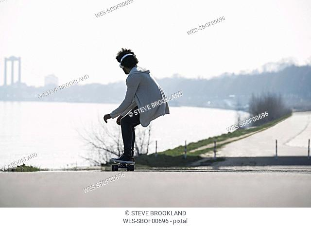 Young man riding longboard at the riverside