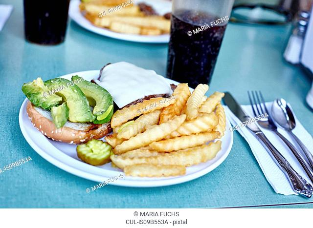 Burger and chips with cola on cafe table, New York City, USA
