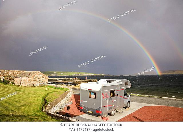 Uyeasound, Unst, Shetland Islands, Scotland, UK, Europe  Motorhome in Gardiesfauld youth hostel campsite with rainbow and grey clouds over the sea  Most...