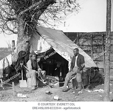 'Contrabands' of the Union Army during the Civil War sitting in front of a tent, one with cigar and the other with a soup ladle