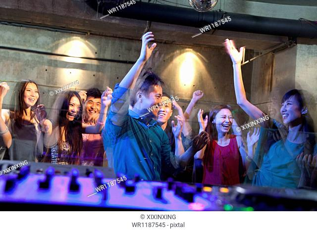 A view from DJ's deck of a crowd dancing in nightclub