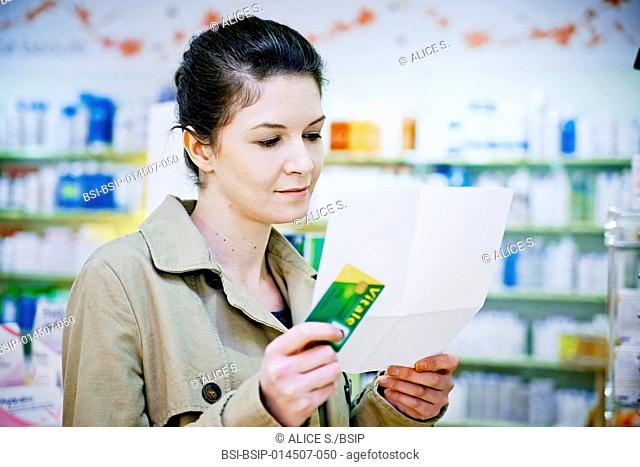 Woman holding her medical insurance card and a prescription