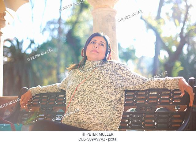 Mature woman sitting bench wearing headphone looking away, Seville, Spain