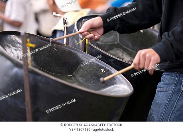 A young man keeps tune as a bangs away on his steel drum as part of the drum band
