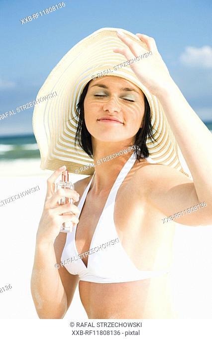 woman applying perfume on beach