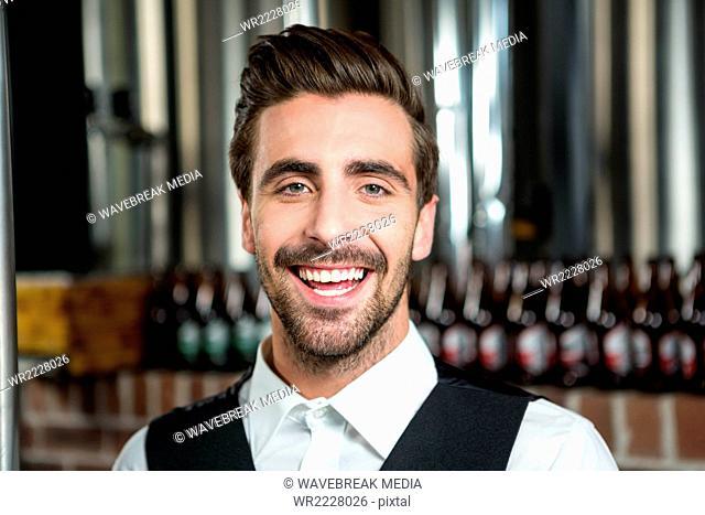 Handsome barman smiling at camera