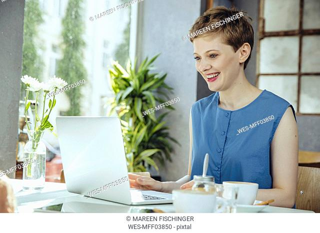 Smiling woman working in cafe with her laptop