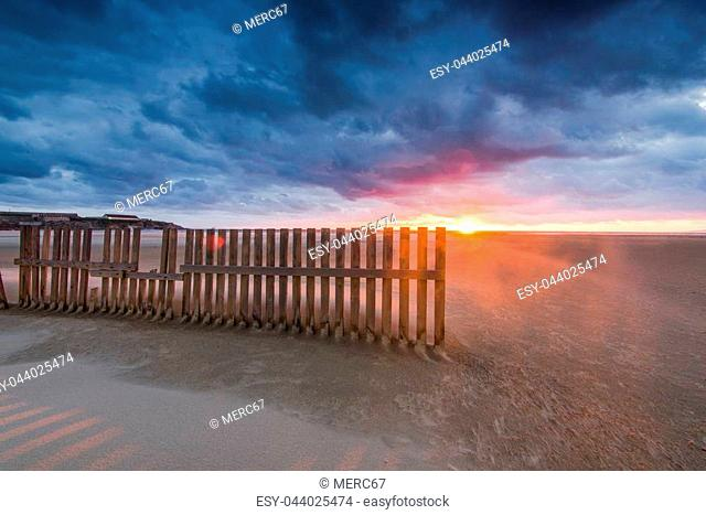 wooden fences on beach in Tarifa, Spain sunset after dramatic storm. Famous surf and kite spot known for strong winds