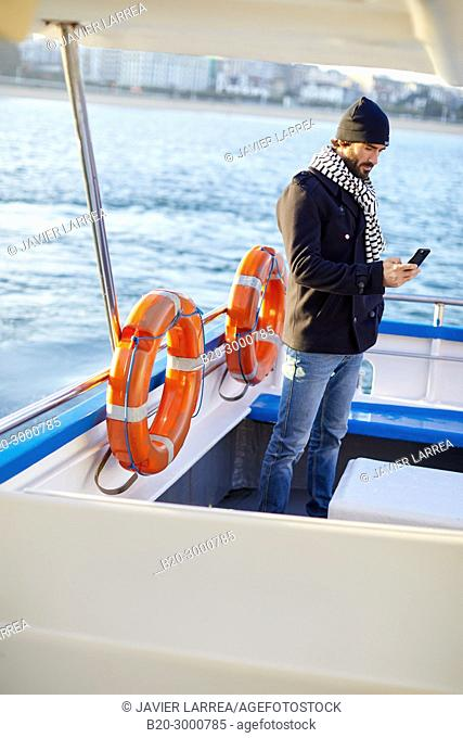Adult man on a boat trip to Santa Clara Island, La Concha Bay, Donostia, San Sebastian, Gipuzkoa, Basque Country, Spain, Europe, Winter