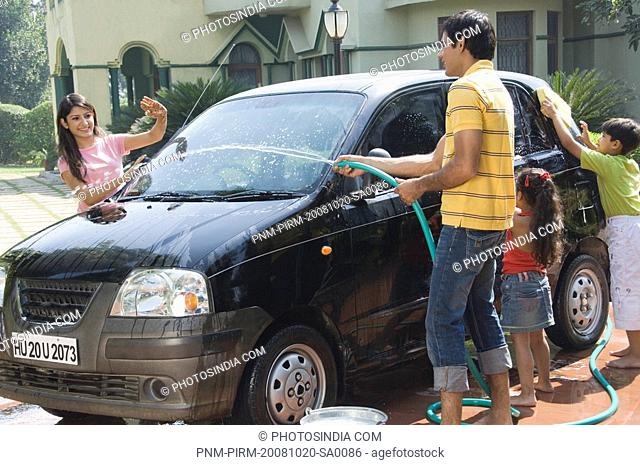 Man spraying water on his wife while his children washing a car, New Delhi, India