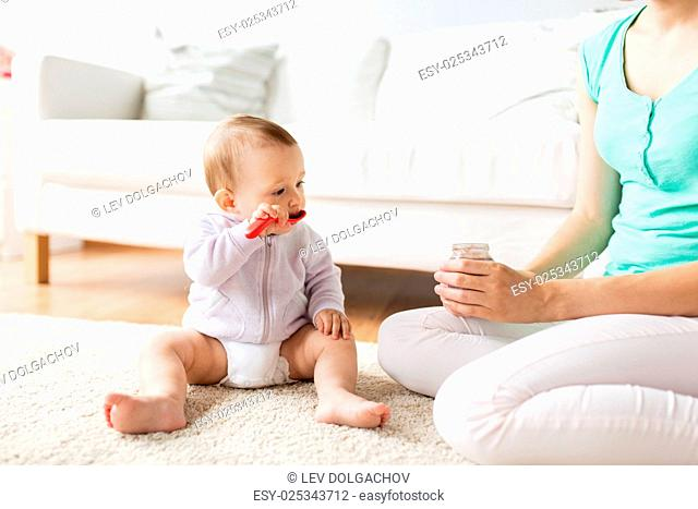 family, food, child, feeding and parenthood concept - mother and baby with spoon eating puree from jar at home