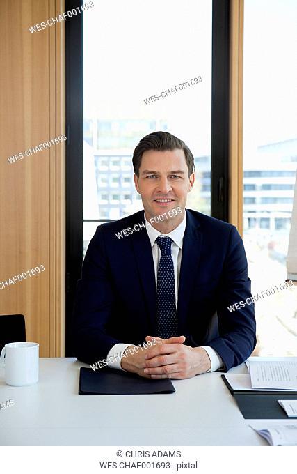 Portrait of confident businessman at office desk