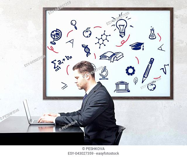 Side view of businessman using laptop at workplace with education icons in frame. Knowledge concept