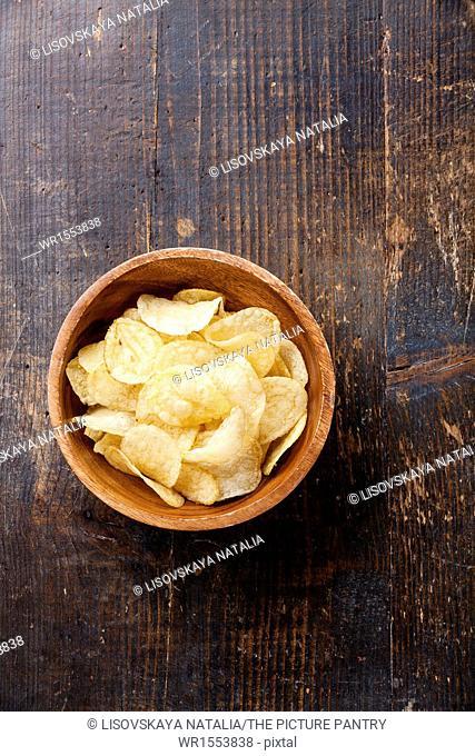 Crispy potato chips on wooden background