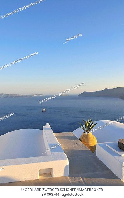 Rooftop terrace and a yellow clay vase with a view over the blue sea, Oia, Ia, Santorini, Cyclades, Greece, Europe