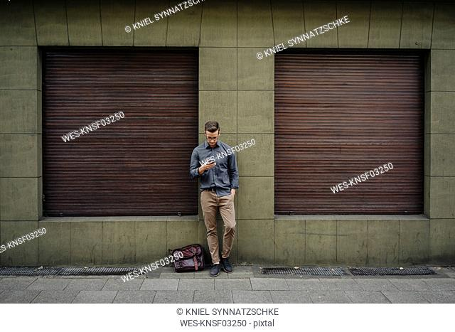 Young man leaning against house front using cell phone