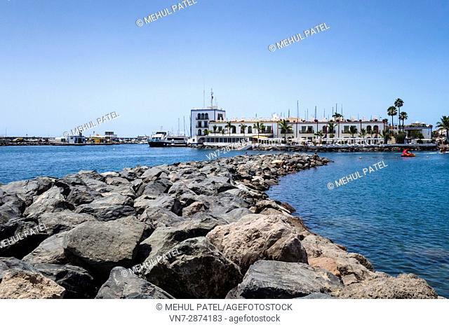 Rocky water barrier and marina of Puerto de Mogan, Gran Canaria, Canary Islands, Spain