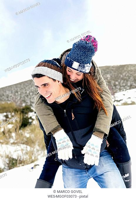 Young man carrying his girl fried piggyback in winter