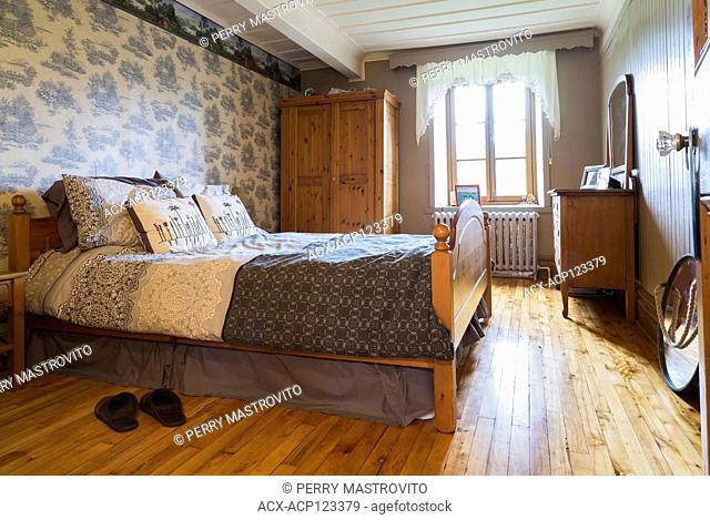 Master bedroom with queen size bed inside an old circa 1752 Canadiana style fieldstone house, Quebec, Canada. This image is property released