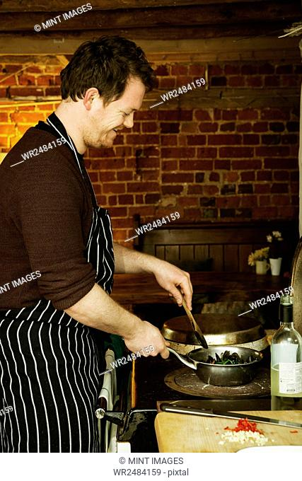 Chef standing in a kitchen, cooking Black Mussels in a pan
