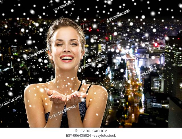 people, holidays, advertisement and luxury concept - laughing woman in evening dress holding something imaginary over snowy night city background