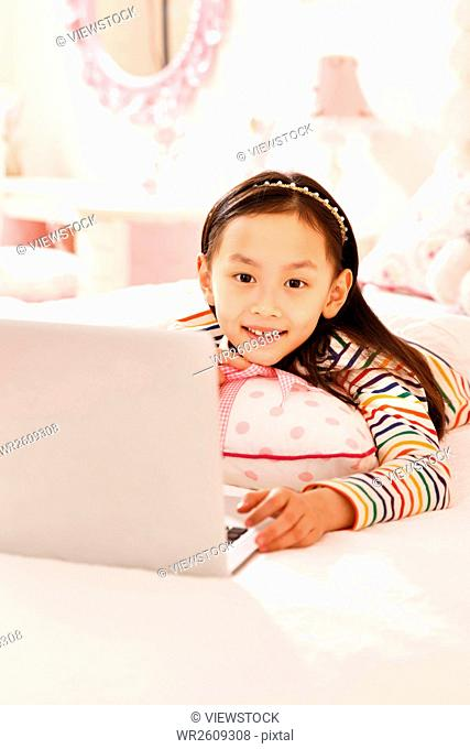 The little girl uses a laptop in bed
