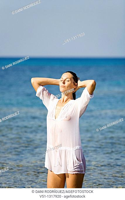 Sensual brunette woman with a wet shirt in the water