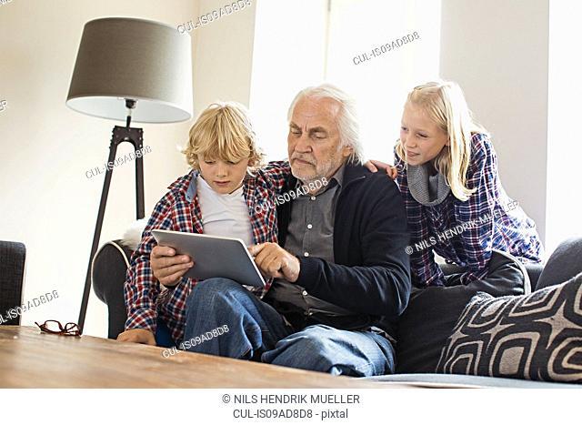 Grandfather using digital tablet with grandchildren
