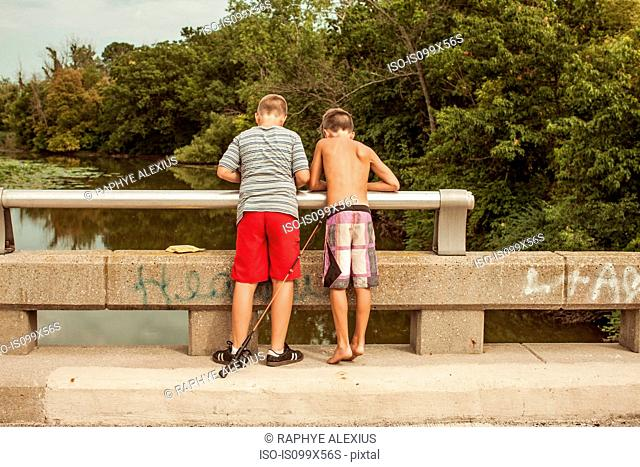 Boys on bridge with fishing rod