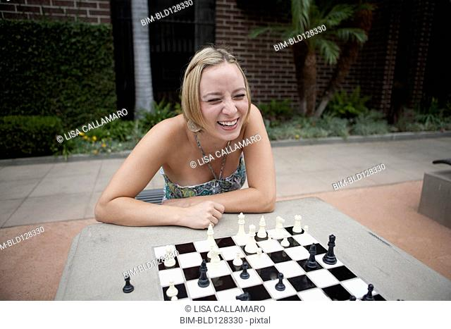 Caucasian woman playing chess in urban park