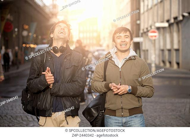 Two young people laughing in the street