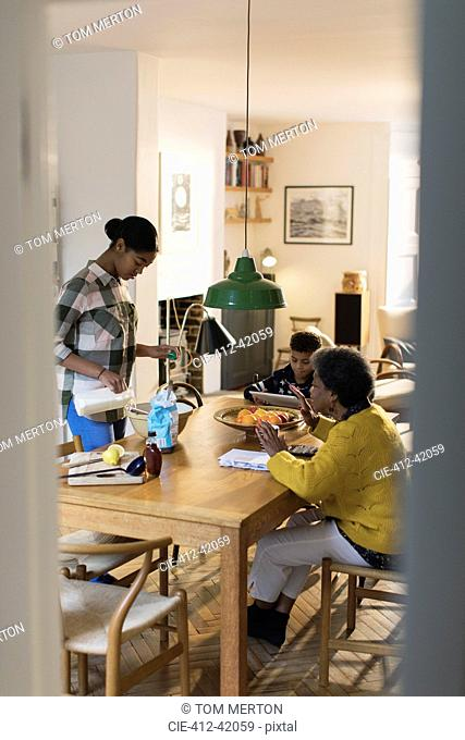 Grandmother and grandchildren baking at dining table