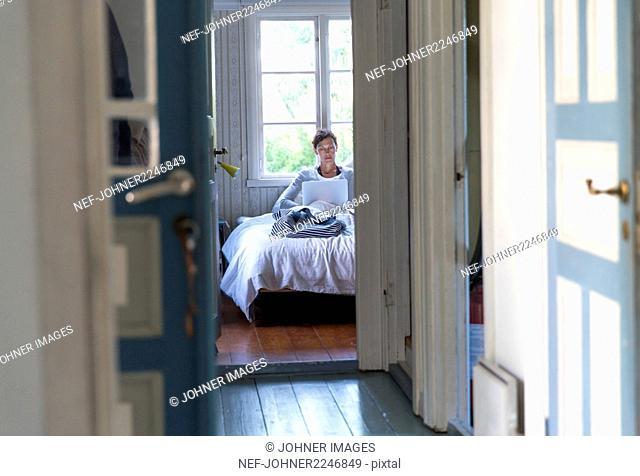 Woman in bedroom using laptop