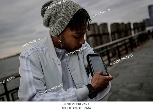 Young man training on riverside at dawn using smartphone touchscreen