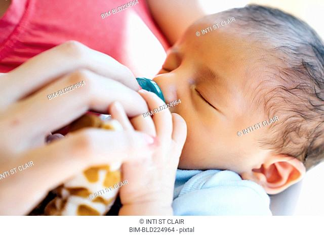 Hispanic woman holding baby boy with pacifier