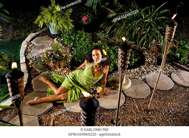 Young Hispanic woman in green dress relaxing in tropical garden with tiki torches