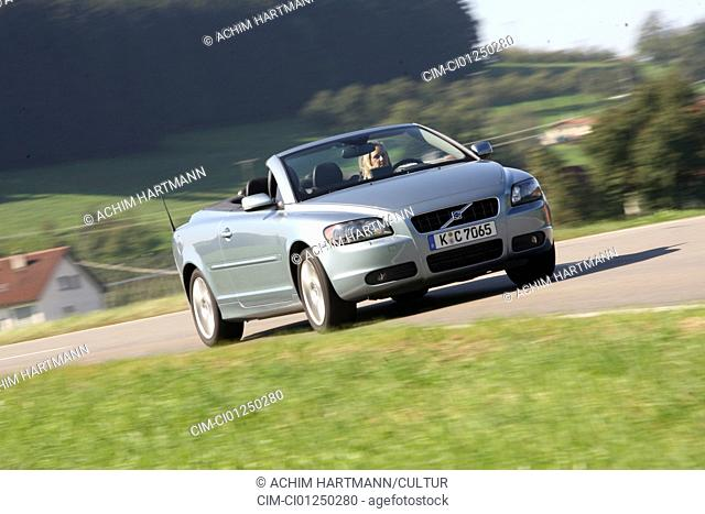Volvo C70 T5 Summum, model year 2006-, silver, driving, diagonal from the front, frontal view, country road, open top