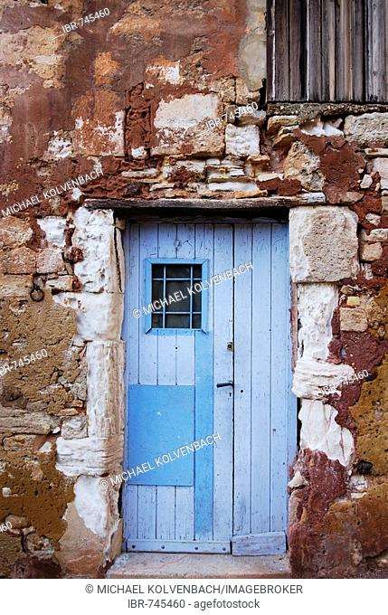 Blue door on an old red stone wall in Roussillon, Provence, South of France