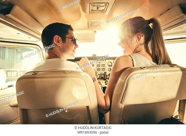 Young couple sitting in cockpit of propeller airplane