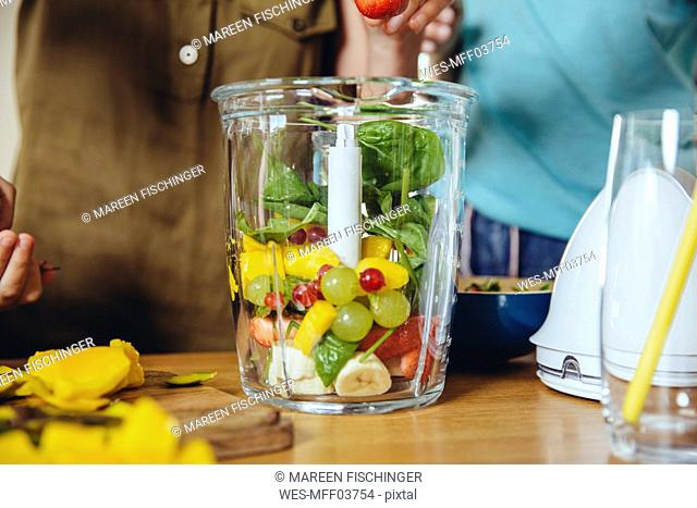 Close-up of mother and children putting fruit into a smoothie blender