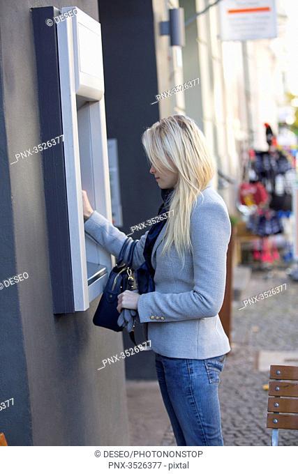 Pretty blonde woman using a cash machine