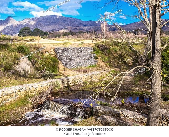 """River and embankment gabions. Wire """"cages"""" built to hold the loose stone embankment from collapsing into the water. Cape Town, South Africa"""
