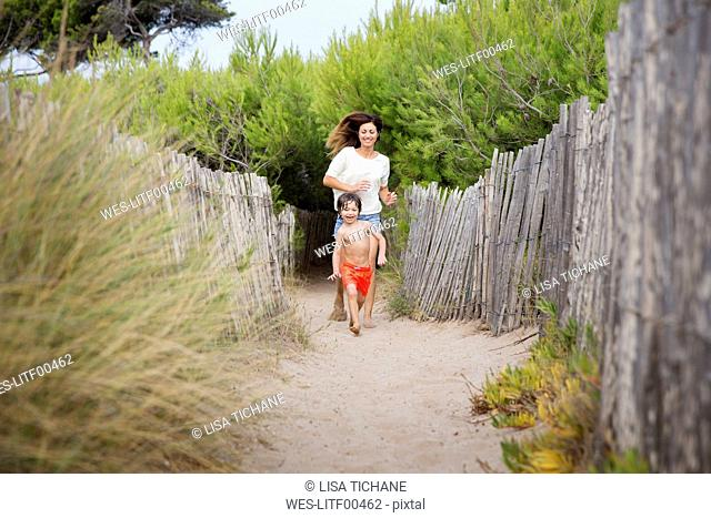 Happy mother and son running on beach path