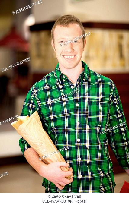 Man carrying baguette in grocery store