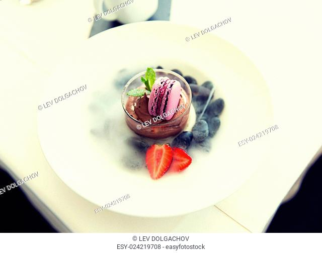 food, culinary, haute cuisine and cooking concept - close up of chocolate dessert with macaron cookie and fresh strawberry at restaurant
