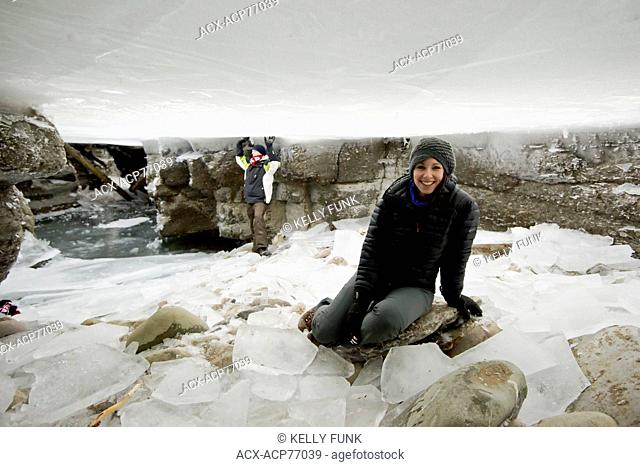 A young woman is under the frozen Maligne River, which freezes, then water levels drop. Maligne Canyon, Jasper National Park, Alberta, Canada