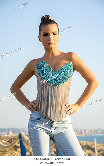 Beautiful young slim woman wearing a corset standing outdoors