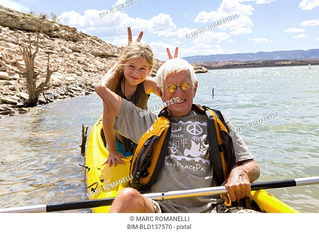 Older Caucasian man posing in kayak with granddaughter